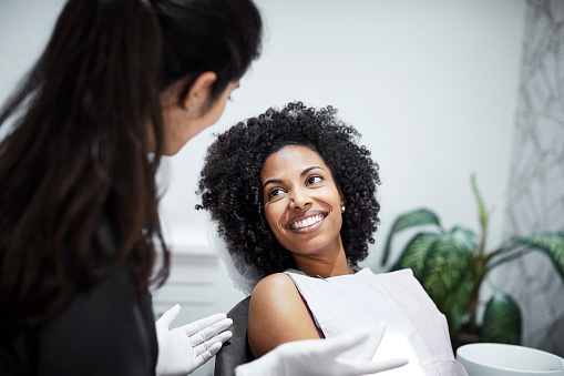 Beautiful Black woman with dental assistant at SmileCOS Dentistry in Colorado Springs, CO